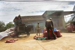 Männer, die an sortierender Maschine der Kaffeebohnen auf Straße am 11. Februar 2012 in Nam Ban, Vietnam arbeiten Stockfoto