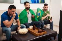 Männer, welche im Fernsehen die Olympics aufpassen Stockfoto