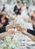 Människahänder som anknyter exponeringsglas med vitt vin Arkivbilder