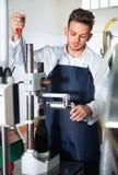 Männliche Arbeitskraft, die Weinflaschen mit Maschine an Sekt bekorkt Stockfotos