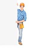Männliche Arbeitskraft mit dem Sturzhelm, der hinter einem Panel aufwirft Stockfotos