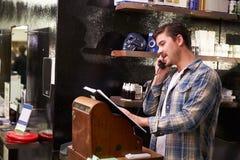 Männliche Barber Standing By Cash Register, die Anmeldung nimmt Stockfotografie