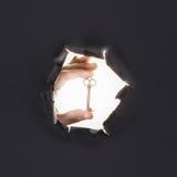Männliche Hand, die durch den grauen Papierhintergrund bricht und Schlüssel hält Stockbilder