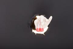 Männliche Hand, die durch den Papierhintergrund bricht und Reagenzglas hält Stockfotografie