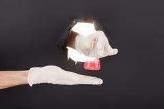 Männliche Hand, die durch den Papierhintergrund bricht und Reagenzglas hält Stockbild