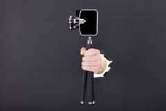 Männliche Hand, die durch den schwarzen Papierhintergrund bricht und Retro- Kamera hält Lizenzfreies Stockfoto