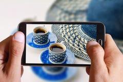 Männliche Hand, die Foto der SommerKaffeepause, des weiblichen Strohhutes und zwei Tasse Kaffees mit Zelle, Handy macht Stockbild
