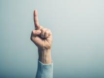 Männliche Hand mit dem Finger, der oben zeigt Stockbild