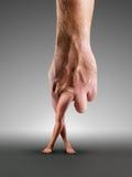 Männliche Hand mit den Beinen Stockfotografie