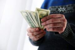 Männliche Hände, die US-Dollars halten Stockbilder