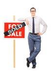 Männliche Immobilienagentur, die auf einem Verkaufszeichen sich lehnt Stockfotos
