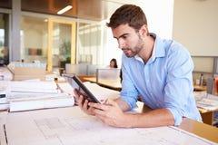 Männlicher Architekt With Digital Tablet, das Pläne im Büro studiert Stockbilder