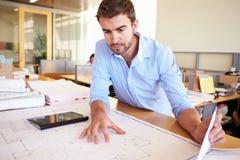 Männlicher Architekt With Digital Tablet, das Pläne im Büro studiert Stockfotografie