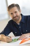 Männlicher Architekt Working On Blueprint am Schreibtisch Stockfotos
