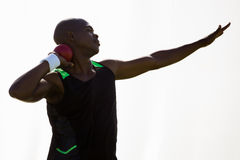 Männlicher Athlet, der sich vorbereitet, Kugelstoßenball zu werfen Lizenzfreies Stockfoto