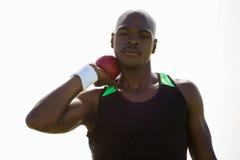 Männlicher Athlet, der sich vorbereitet, Kugelstoßenball zu werfen Stockbilder