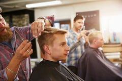 Männlicher Barber Giving Client Haircut In-Shop Lizenzfreies Stockfoto