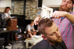 Männlicher Barber Giving Client Haircut In-Shop Stockfotos
