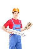 Männlicher Bauarbeiter, der einen Ziegelstein und einen Plan hält Stockbilder
