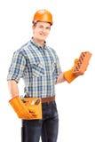 Männlicher Bauarbeiter mit dem Sturzhelm, der einen Ziegelstein hält Lizenzfreies Stockfoto