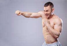 Männlicher Boxer, der Trainingsdurchschläge auf Grau macht Stockfotografie