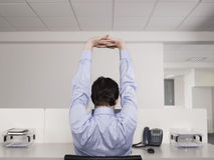 Männlicher Büroangestellter, der am Schreibtisch ausdehnt Stockbilder