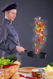 Männlicher Chef, der Gemüse vom Wok in der Küche wirft Stockfotos