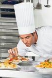 Männlicher Chef Garnishing Pasta Dishes Stockbilder