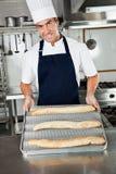Männlicher Chef Presenting Baked Loafs in der Küche Stockfoto