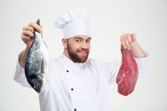 Männlicher Chefkoch, der frische Fische und Fleisch hält Stockfotos