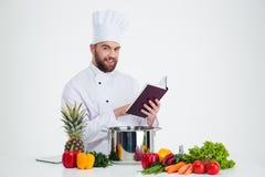 Männlicher Chefkoch, der Rezeptbuch hält und Lebensmittel zubereitet Lizenzfreies Stockfoto