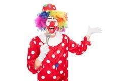 Männlicher Clown, der über ein Mikrofon spricht Stockfotografie