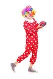 Männlicher Clown mit frohem Ausdruck auf seinem Gesicht, das ein Geschenk hält Stockfotografie