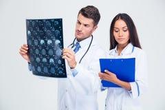 Männlicher Doktor, der Röntgenstrahlbild des Gehirns betrachtet Stockbilder