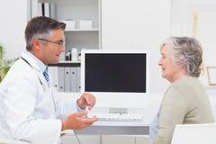 Männlicher Doktor, der sich bei Tisch mit älterem Patienten unterhält Stockfotografie