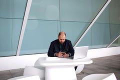 Männlicher Entwickler, der nach der Arbeit am Handy auf Laptop-Computer plaudert, beim Sitzen im modernen Büroinnenraum, Stockfotografie