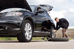Männlicher Fahrer, der seinen Reifen am Straßenrand ändert Lizenzfreies Stockbild