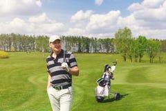 Männlicher Golfspieler, der an der Fahrrinne auf Golfplatz steht Stockfoto