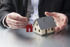 Männlicher Grundstücksmaklerzustand, der den neuen Hauseigentümern Schlüssel gibt Stockbilder