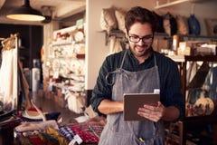 Männlicher Inhaber des Geschenkladens mit Digital-Tablet Stockbilder