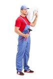 Männlicher Klempner, der eine Toilette trägt Stockfoto