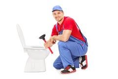 Männlicher Klempner, der nahe bei einer Toilette sitzt und einen Kolben hält Stockfotografie
