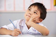 Männlicher Kursteilnehmer, der am Schreibtisch in der chinesischen Schule arbeitet Lizenzfreie Stockfotos