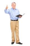 Männlicher Lehrer, der ein Buch anhält und einen Daumen aufgibt Lizenzfreie Stockbilder