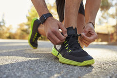Männlicher Läufer, der in der Straße oben bindet seinen Sportschuhabschluß hockt Stockfotografie