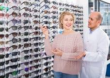 Männlicher Optiker, der reifen blonden Kunden nahe Sonnenbrille konsultiert Stockbilder