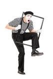 Männlicher Pantomimekünstler, der durch einen Metallrahmen geht Lizenzfreies Stockfoto