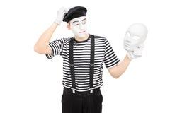 Männlicher Pantomimekünstler, der eine Theatermaske hält Stockbilder