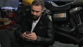 Männlicher Radfahrer benutzt sein Telefon nahe dem Zerhacker an der Motorradwerkstatt stock footage