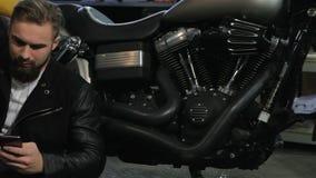 Männlicher Radfahrer schreibt auf seinem Smartphone nahe dem Motorrad stock video